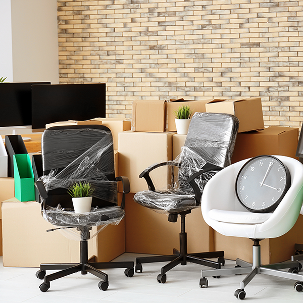 moving boxes and wrapped office furniture in an office building